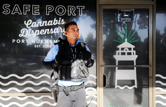 Security guard Ivan Jaurigui stands outside by the door of Safe Port Cannabis Dispensary in Port Hueneme. A year after recreational pot sales were made legal, the four marijuana dispensaries in Port Hueneme have been doing well and making money for the city.