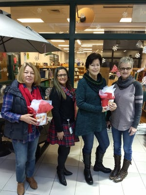 (From left) Linda Finch, a member of Rutgers Master Gardener of Cumberland County, Arlene Maggioncalda, guidance counselor for Silver Run Elementary School in Millville, Kathy Geiger, member, RMGCC, and Pamela Burton, director, RMGCC, present holiday baskets to two students on Dec. 20. The funds for the baskets were raised on a coach tour to the Philadelphia Fairmount Park Mansion and center city holiday sites sponsored by RMGCC.
