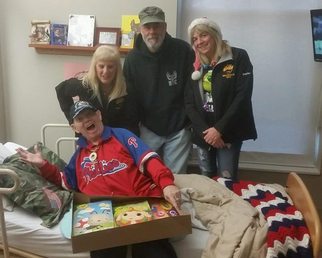Members of the Millville Elks Lodge #580 (standing, from left) Arleen Hickman, Exalted Ruler, Darlene Klawitter, trustee, and Keith Rafine, veterans chairman, brought their holiday spirit and gifts to veterans at the New Jersey Veterans Memorial Home in Vineland.