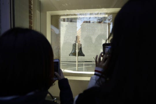 Tourists to Independence National Historical Park take photographs through a window of the closed building housing the Liberty Bell, Wednesday, Dec. 26, 2018, in Philadelphia. The building is closed due to the partial government shutdown. (AP Photo/Matt Slocum)