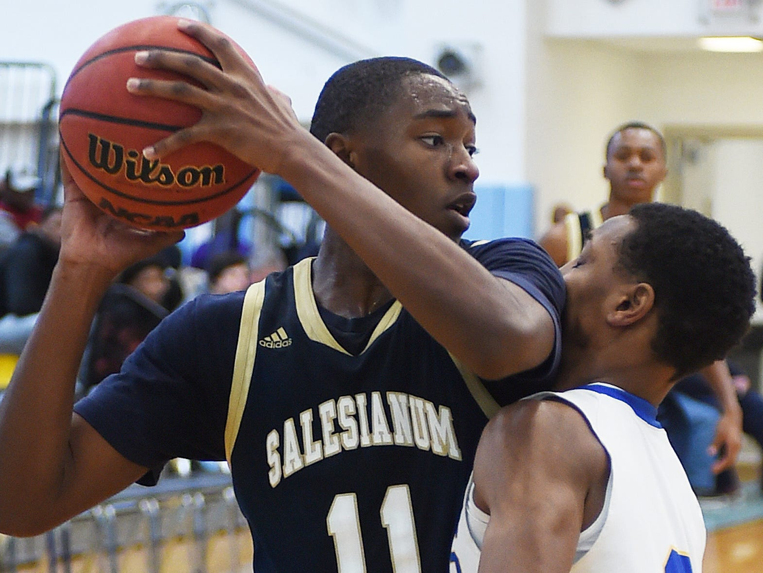 Sallies #11 Darnell Vaughan hits the chin of CR's #3 William Scott as Slam Dunk to the Beach kicked off on Thursday December 27th with the opening game of Caesar Rodney playing Salesianum at the tournament held at Cape Henlopen High School.