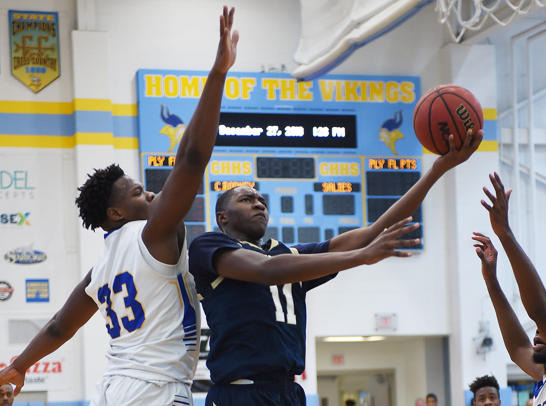 Sallies #11 Darnell Vaughan goes for a basket over CR's #33 William Burke as Slam Dunk to the Beach kicked off on Thursday December 27th with the opening game of Caesar Rodney playing Salesianum at the tournament held at Cape Henlopen High School.