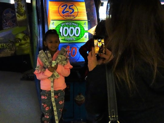 A'yonne Sayles smiles for a picture after winning the jackpot 1,000 tickets on the Big Bass Wheel game at Blits.