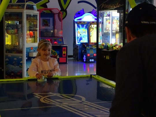 Ali Walter plays air hockey with her grandfather Leslie Walter at Blits.