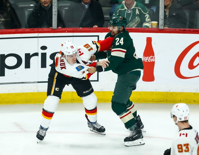 Minnesota Wild defenseman Matt Dumba, right, fights the Calgary Flames' Matthew Tkachuk in the first period on Dec. 15. He didn't return for the second period.