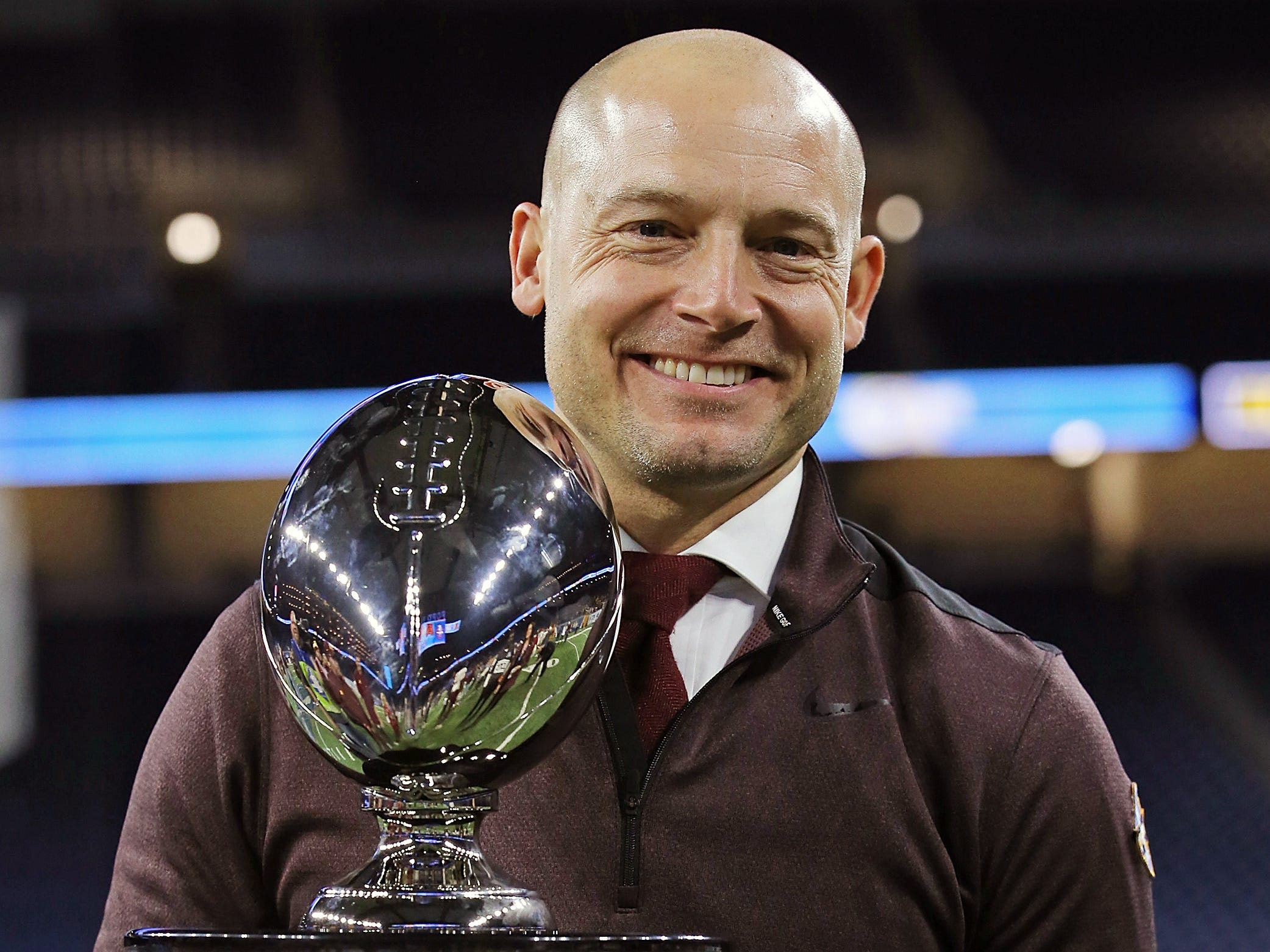 Minnesota coach P. J. Fleck holds the Quick Lane Bowl trophy after defeating Georgia Tech, 34-10, at Ford Field.