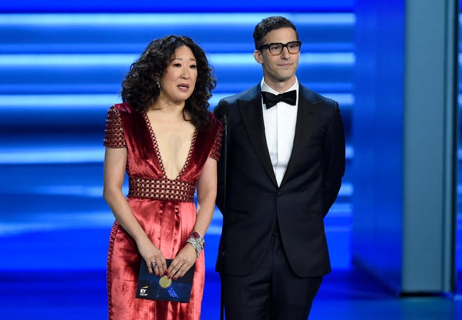 Sandra Oh, left, and Andy Samberg, seen here presenting at September's Emmy Awards, will team up again to co-host NBC's Golden Globe Awards on Jan. 6.