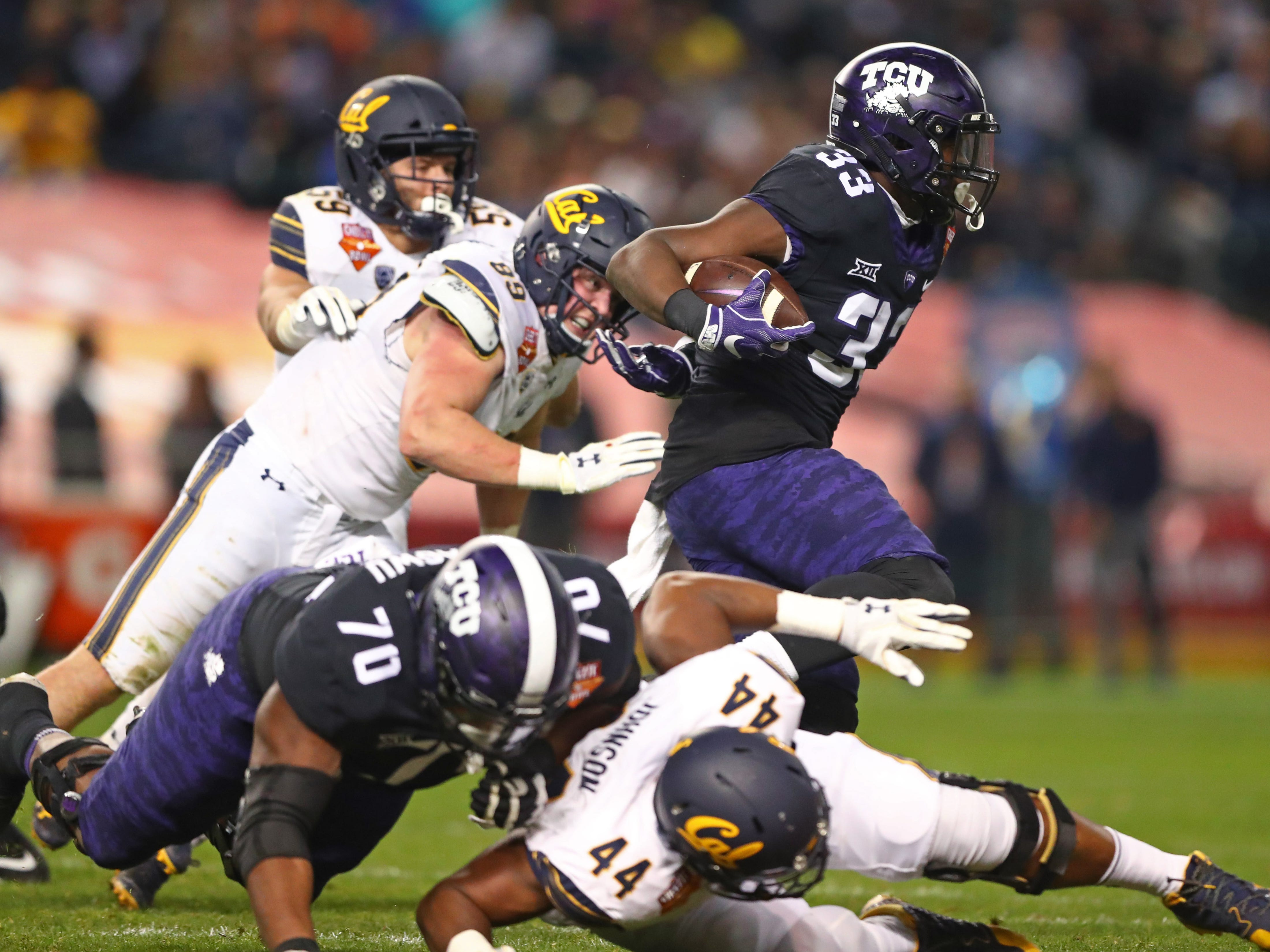 TCU running back Sewo Olonilua (33) runs against California in the Cheez-It Bowl at Chase Field.