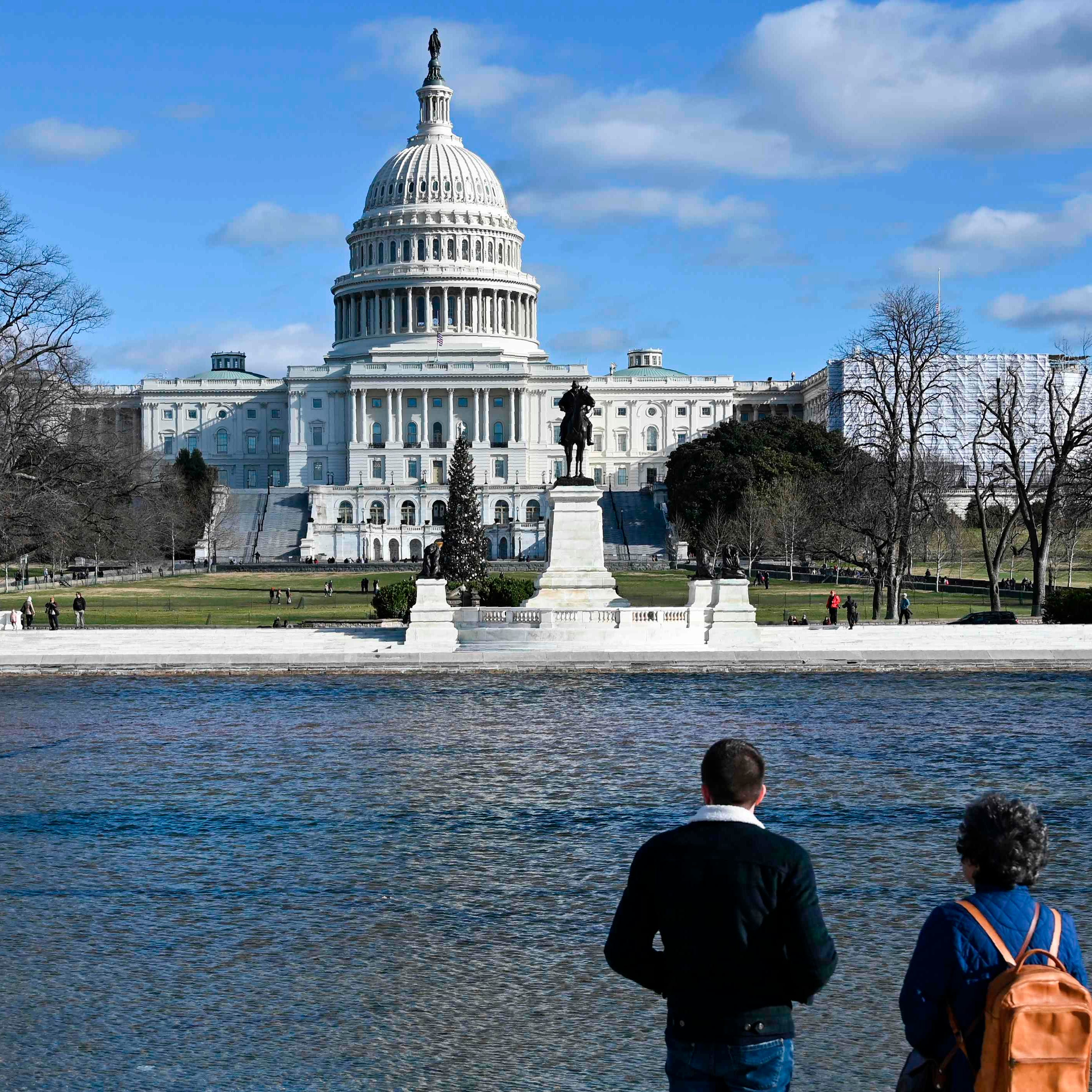 Tourists look at the U.S. Capitol in Washington, on Dec. 22, 2018, as the government continues in a partial shutdown.