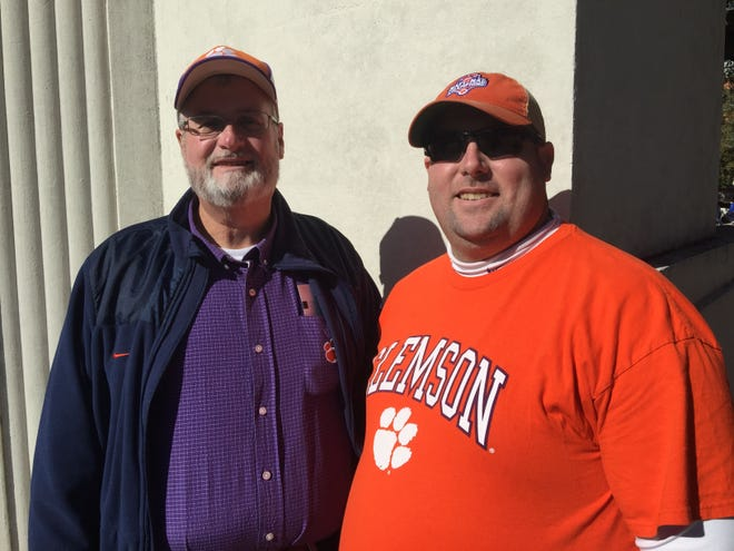 Clemson Football fans Eddie McCurry and his son Trey McCurry pose for a photo at the John F. Kennedy Memorial in Dallas on Friday, Dec. 28, 2018, ahead of the Tigers' Cotton Bowl match-up with Notre Dame on Saturday.
