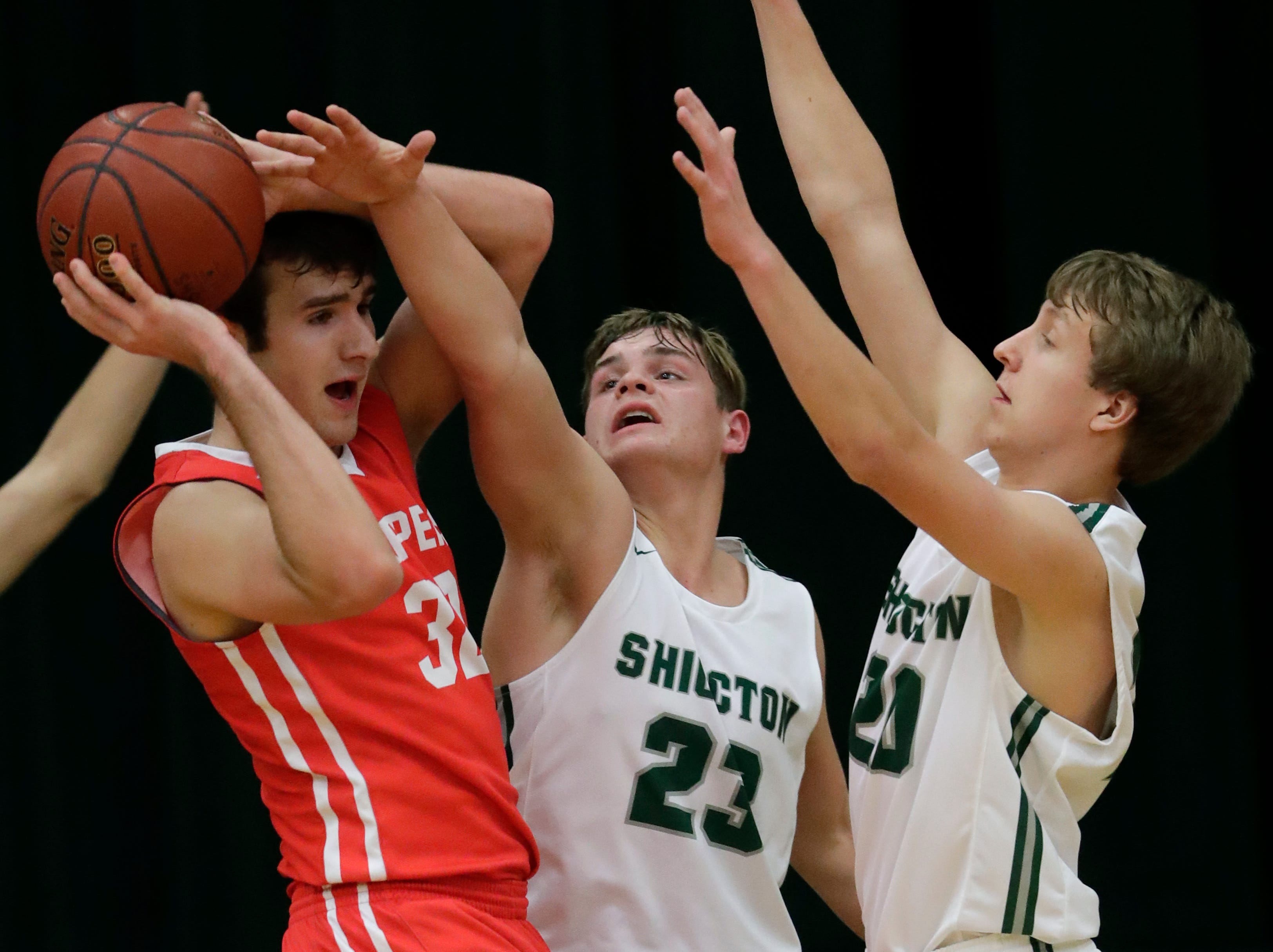Sturgeon Bay High School's Carson Talbert (32) is under heavy pressure by Shiocton High School's Deven Bedor (23) and Caden Schmidt (20) during their boys basketball game Thursday, December 27, 2018, in Shiocton, Wis. 