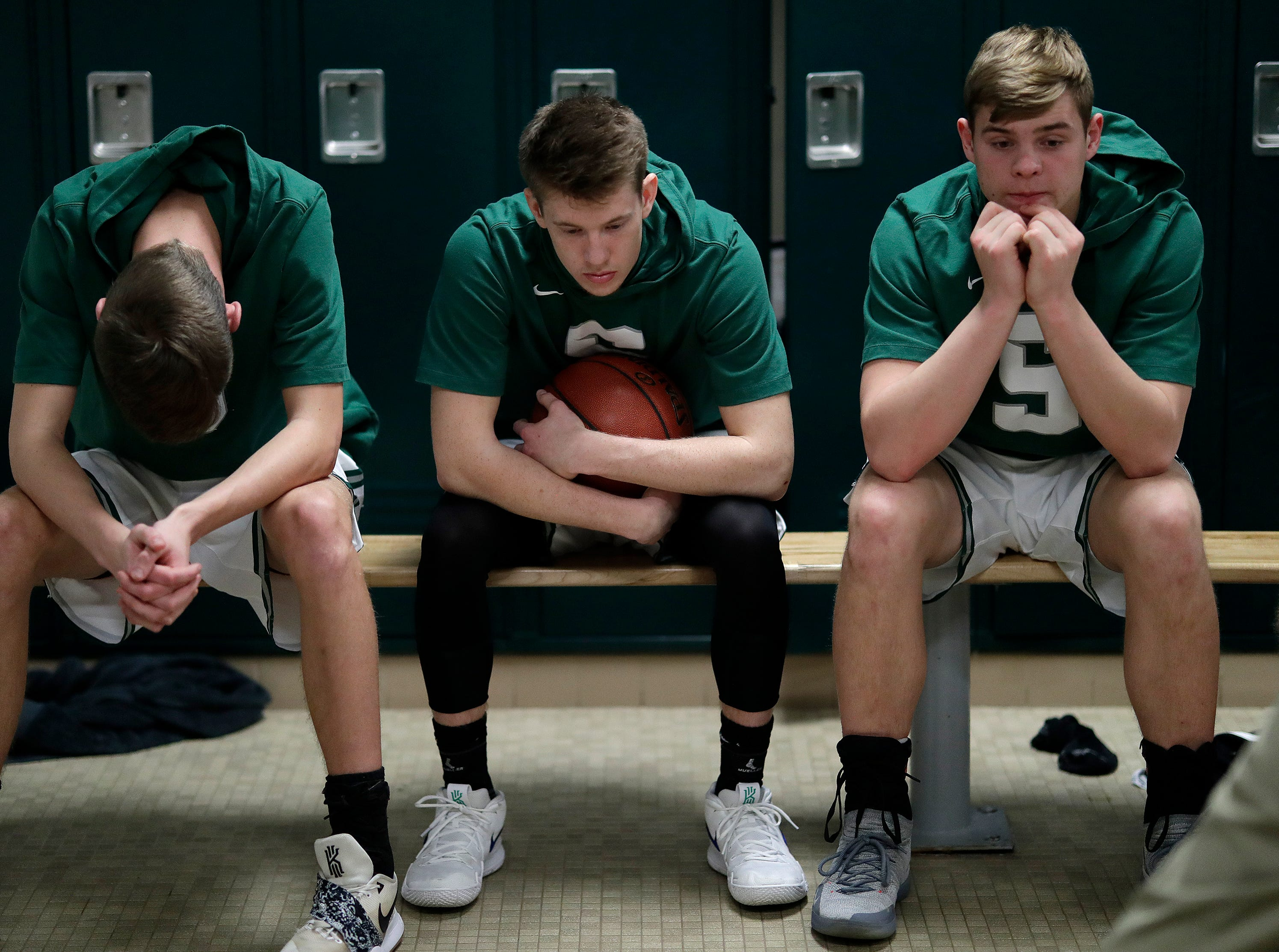 Shiocton High School's Corbin Lorge, left, Jack Fielding and Deven Bedor, right, get mentally prepared in the locker room during the coaches talk prior to playing against Sturgeon Bay High School's basketball team Thursday, December 27, 2018, in Shiocton, Wis. 