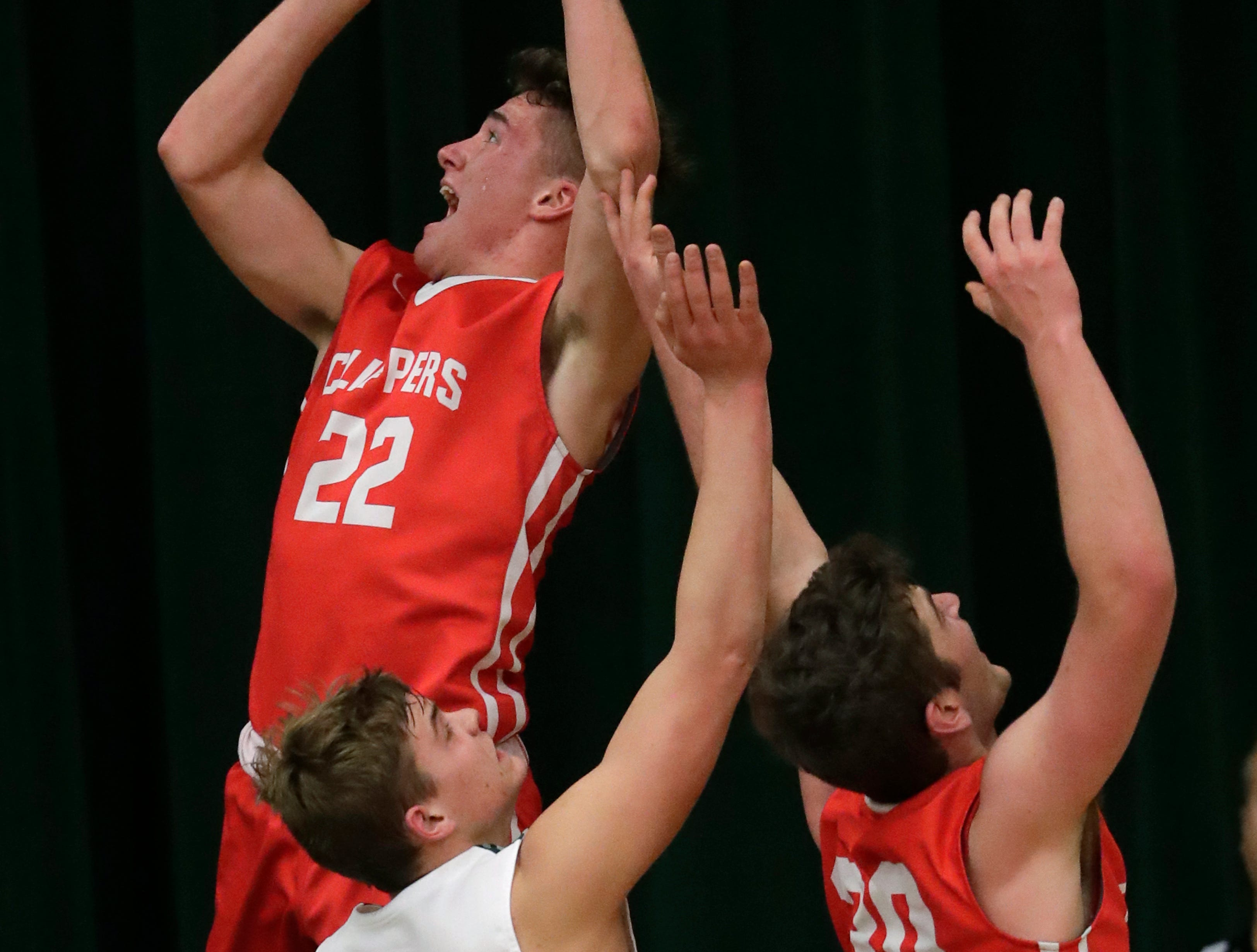Sturgeon Bay High School's Jake Schneider (22) puts up a shot against Shiocton High School's Deven Bedor (23) as Trent Ehlers (30) moves in during their boys basketball game Thursday, December 27, 2018, in Shiocton, Wis. 