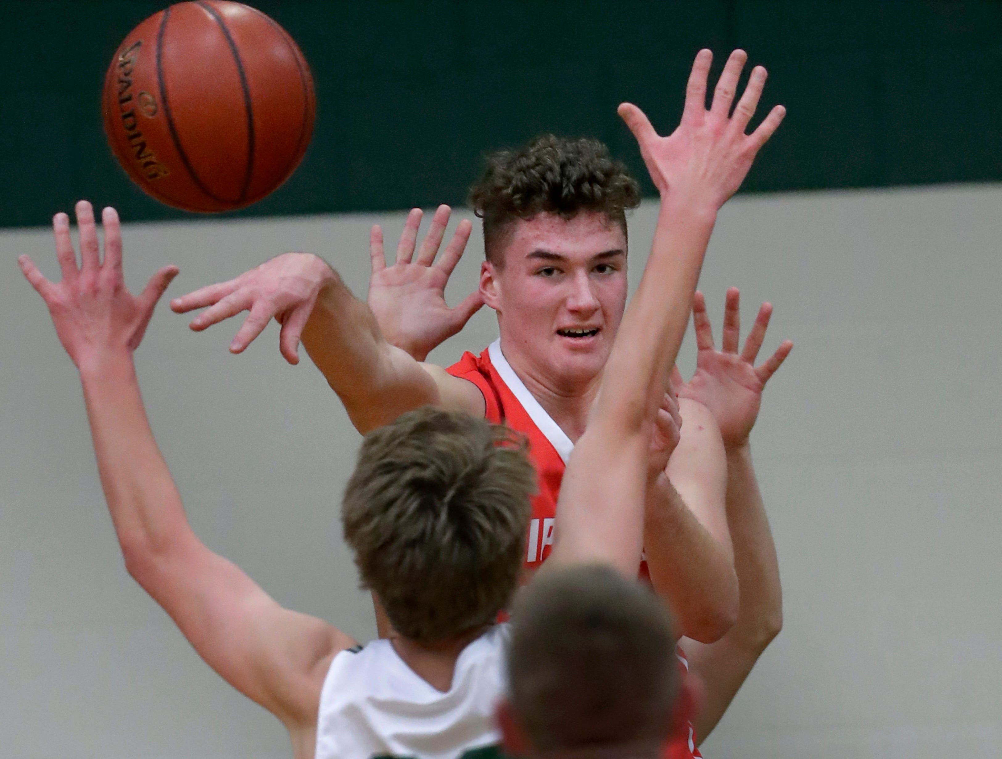 Sturgeon Bay High School's Jake Schneider (222) passes the ball to Gunnar Tebon (14) against Shiocton High School's Caden Schmidt (20) during their boys basketball game Thursday, December 27, 2018, in Shiocton, Wis. 