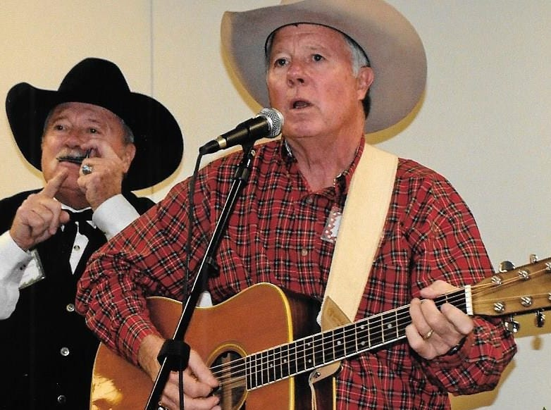 Brothers John Compere of Baird and Mark Compere of San Antonio perform on a Jew's harp and guitar, respectively, at the Cowboy's Christmas Ball in Anson.