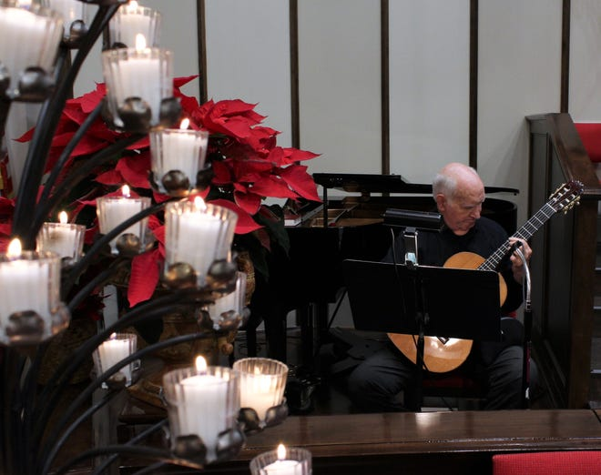 """Dan Mitchell played Christmas season hymns on guitar before First Central Presbyterian Church's Christmas Eve service, then accompanied Larry Wolz on """"Silent Night."""""""