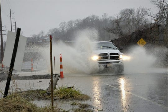 A driver plows through standing water on Lyman Street in the River Arts District.