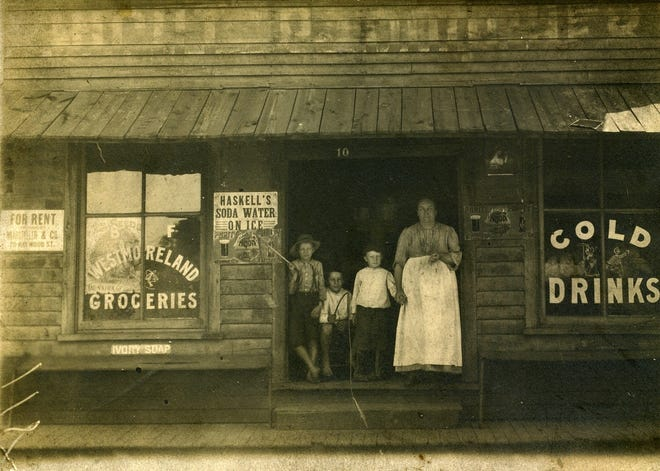 Lillian Moore Westmoreland poses in the doorway of Westmoreland Grocery at 10 Roberts Street, April 1902. Left to right are Ralph Robinson, a family friend; and two sons, Ray and Walter Westmoreland.