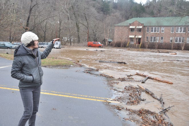 Sculptor Nina Kawar assesses the flooding on Blannahassett Island. Floodwaters prevented the artist from collecting works to show during a planned weekend exhibit in Asheville.