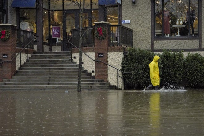 A property manager in Biltmore Village inspects the rising water Friday.
