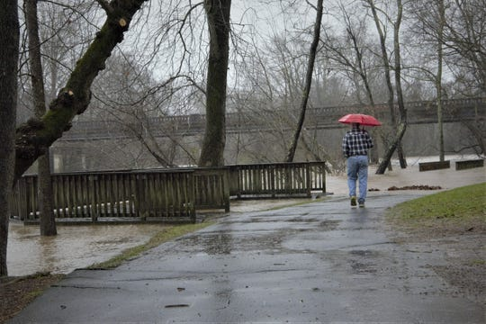 At French Broad River Park, a man walks to the end of a path covered by flood waters.