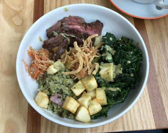 A steak bowl with fried cheese, bamboo rice and greens at All Day Darling.