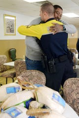 The Rev. Micheal Woods, executive director and CEO of Western Carolina Rescue Ministries, gives Asheville police officer Evan Coward a hug in this 2015 photo after members of the downtown police unit deliver turkeys and other ingredients for the shelter's Thanksgiving meal. Woods said Friday that a change in federal tax law has hurt donations to the agency.