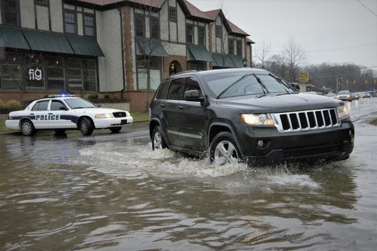 A driver navigates a flooded roadway in Biltmore Village.
