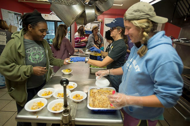 Volunteers serve a meal of tilapia, broccoli, rice and peach cobbler at the Steadfast House, an Asheville-Buncombe Community Christian Ministries shelter for women and children who were formerly homeless, victims of domestic violence or have other housing needs in this 2015 photo. National fears that a tax law change would reduce charitable giving have, for the most part, not been realized at local charities like ABCCM.