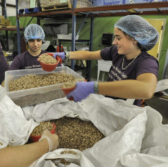Warren Wilson College students fill bags with pinto beans at MANNA Food Bank in this file photo. MANNA officials say it is too soon to say whether a tax law change has reduced donations.