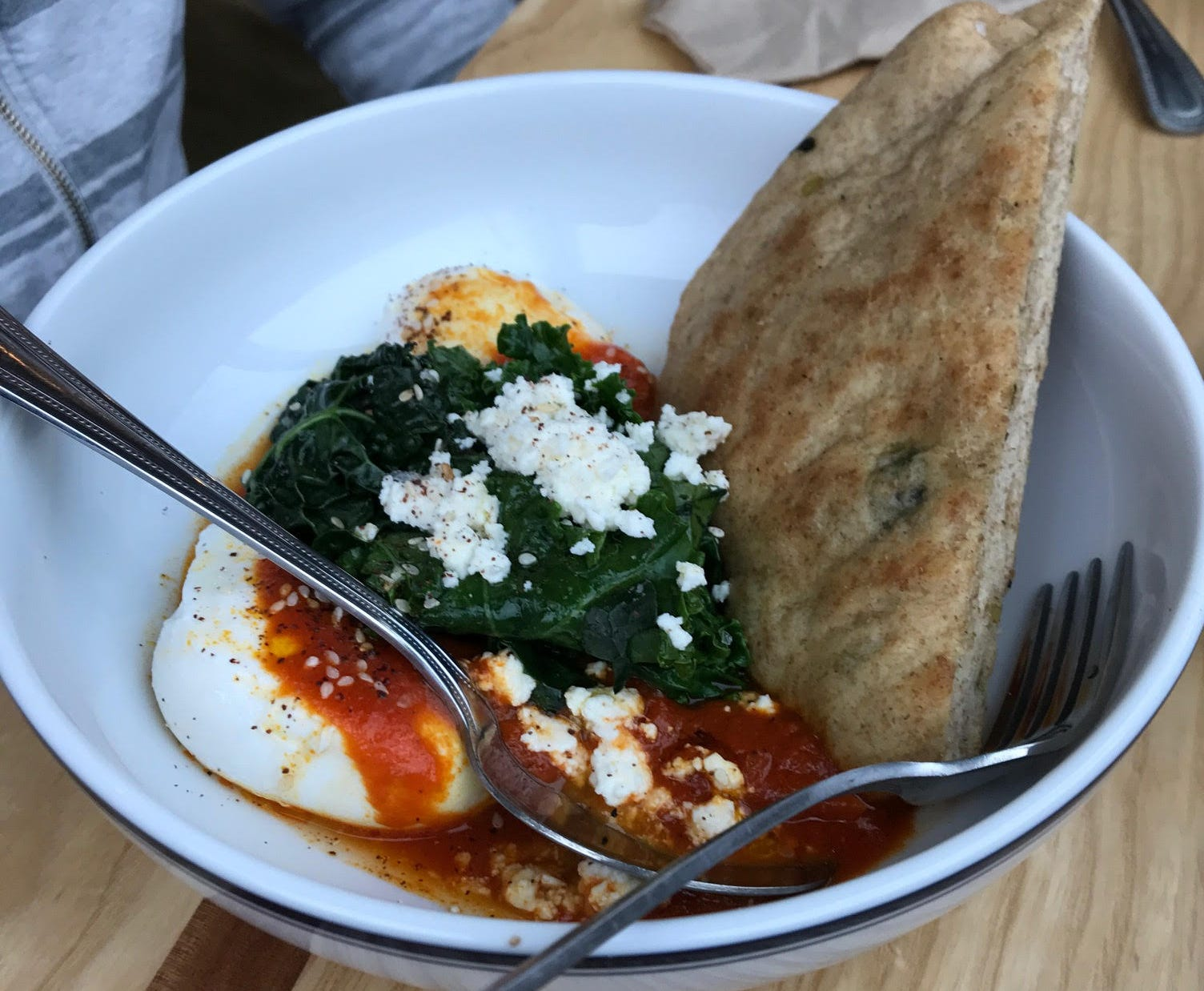 Shakshuka with feta, greens and a wedge of flatbread.