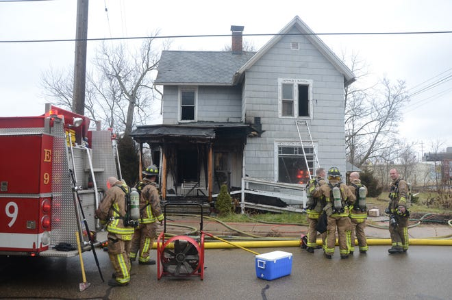 Battle Creek firefighters begin picking up gear after fighting a fire in a vacant house on East Fountain Street Friday morning.