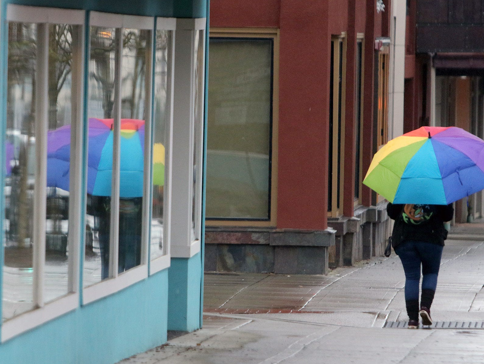 A colorful umbrella is used during an early mornign drizzle along Pacific Ave. in downtown Bremerton on Fridya, December 28, 2018.
