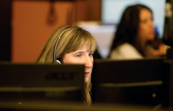 Kitsap CenCom dispatcher Jill Danielsen handles calls on Friday. Kitsap 911 was affected by a CenturyLink outage Thursday that lasted into Friday. Some callers to 911 experienced a busy signal, and CenCom urged callers to reach out to 911 via text or an alternate number.