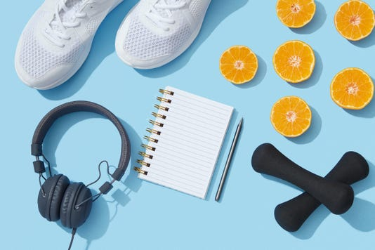 Sports Equipment And Accessories Shoes Dumbbells Notebook And Oranges On Blue Background