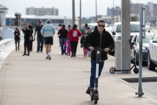 People ride rented motorized scooters along North Shoreline Boulevard on Friday, Dec. 28, 2018.