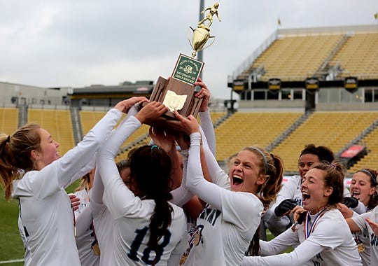 The Cincinnati Country Day girls hoist the Division III Championship soccer trophy after defeating the Kirtland Hornets 3-0 at MAPFRE Stadium in Columbus Friday, Nov. 9, 2018.