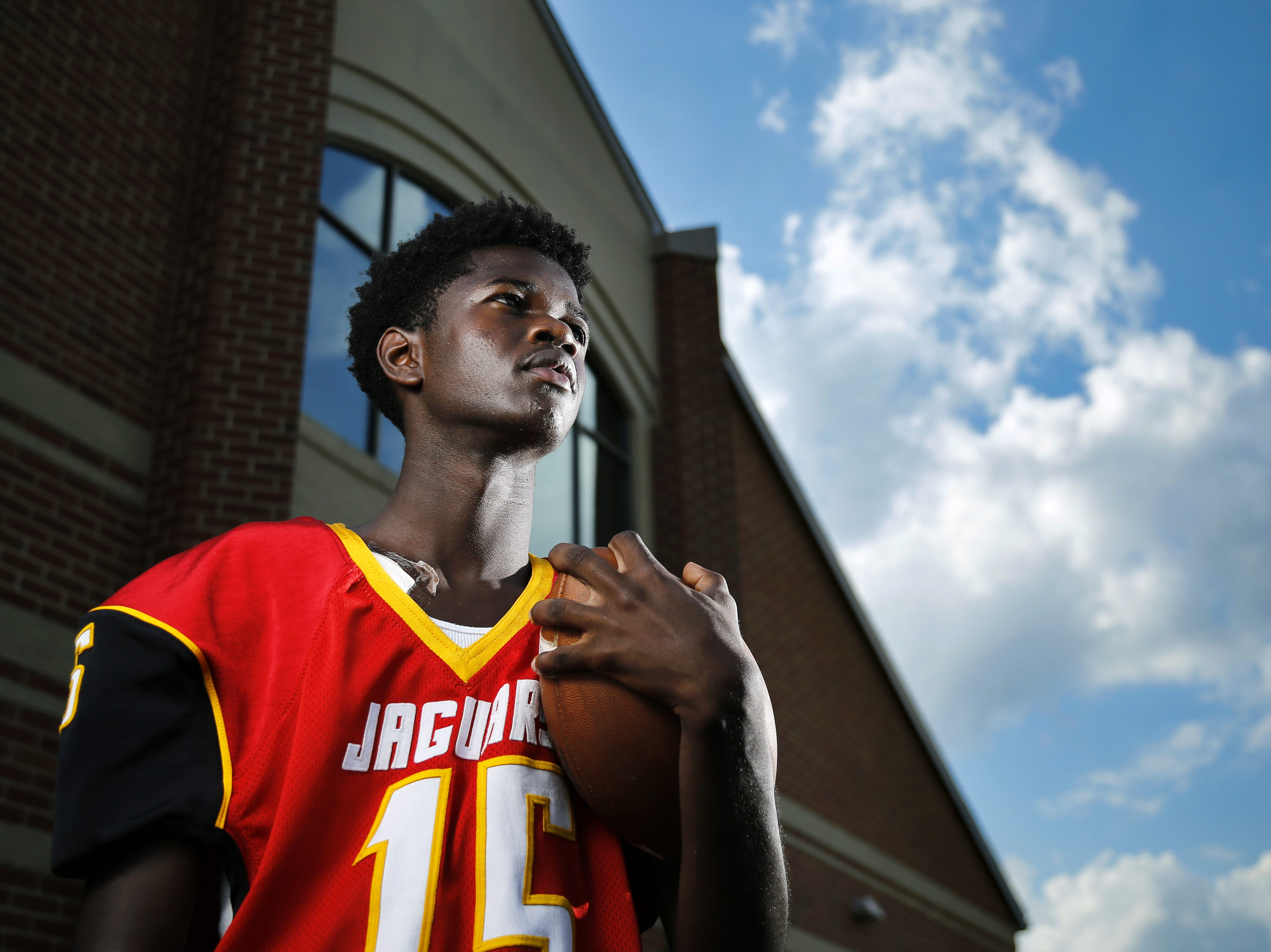 Schroder High School senior Mohammed Bah watches over practice as he poses for a portrait at Schroder High School in Cincinnati on Tuesday, Sept. 18, 2018. The senior kicker will miss the remainder of his senior season after breaking his shoulder on a special teams play.