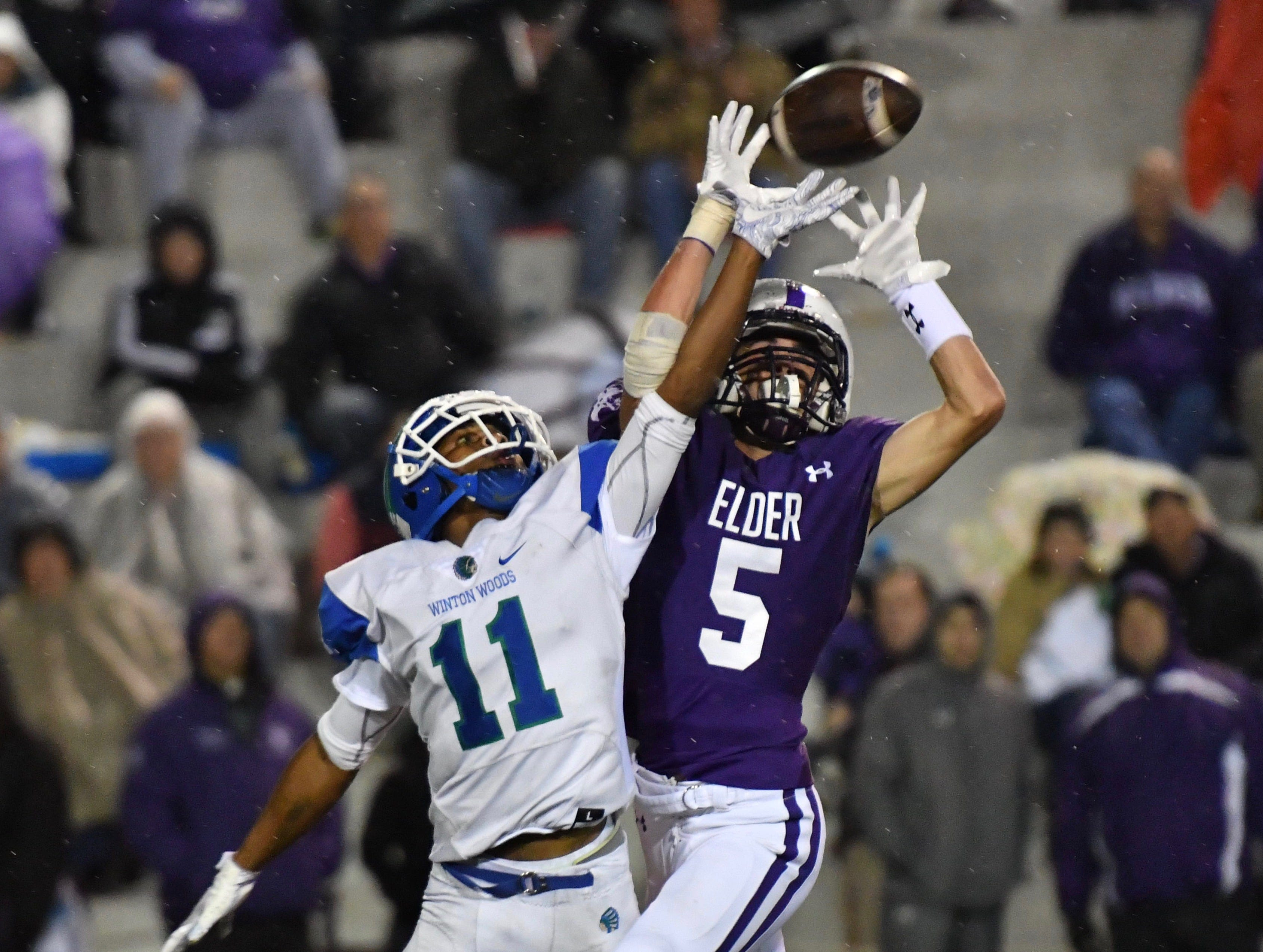 Elder's Sean O'Conner and Winton Woods' Tyquan Fleming battle for a pass in the second quarter Friday, Oct. 12, 2018 at High School