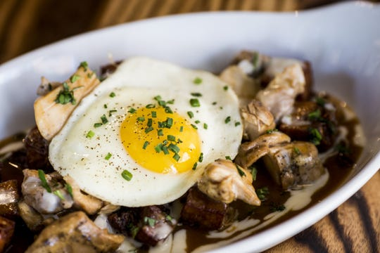 Sacred Beast's hash browns with neck bone gravy, chicken confit and a fried egg.