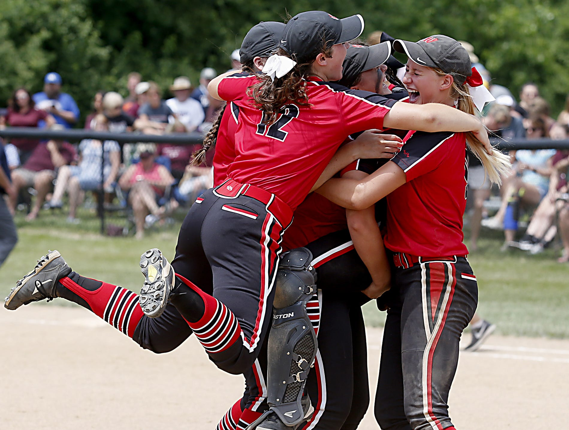 Lakota West infielder Taylor Williams (12) jumps on her teammates after defeating Lebanon 5-0 in their Division I regional softball final at Centerville Saturday, May 26, 2018.