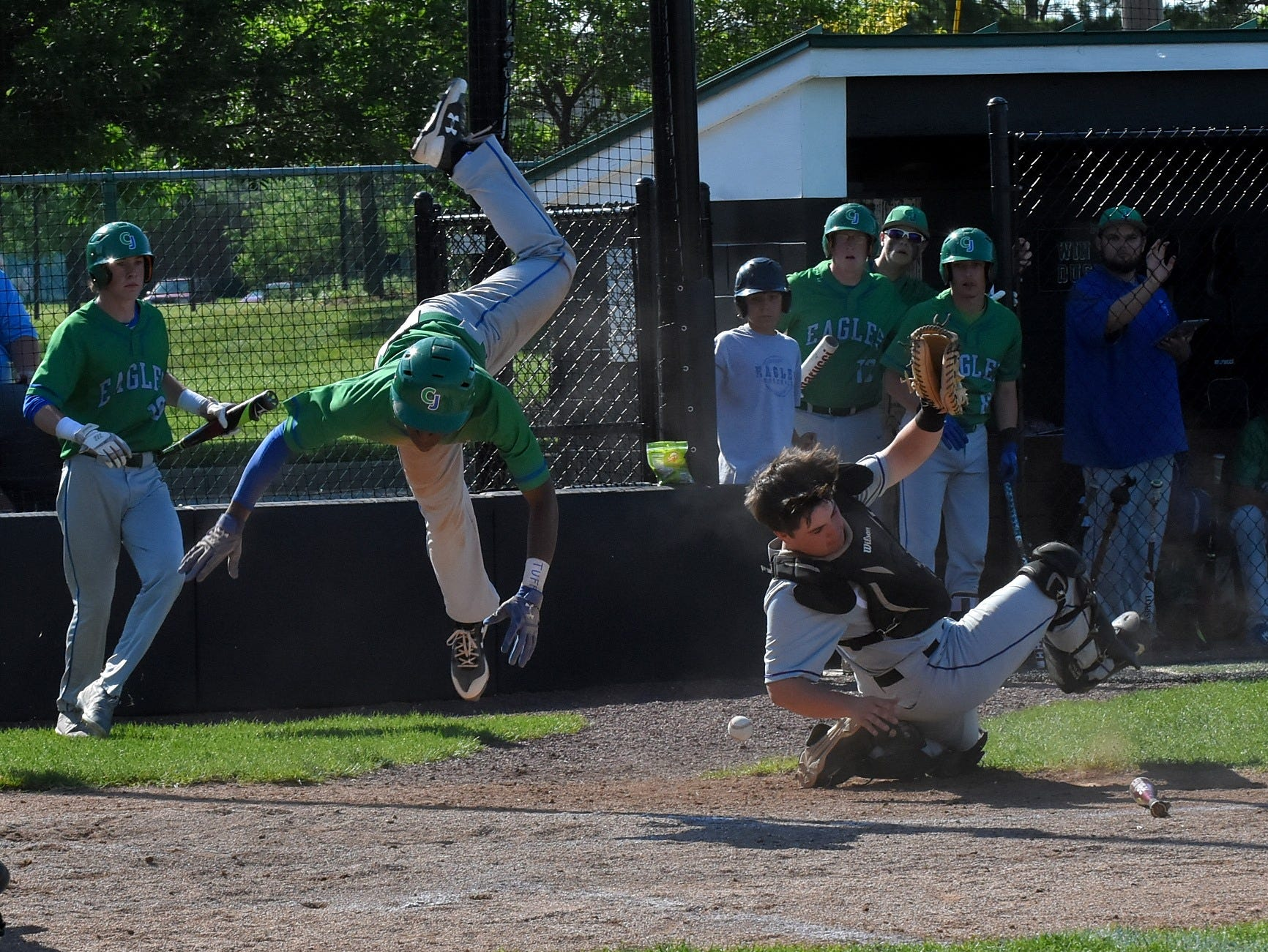 Chaminade's AJ Solomon lands safely at Home after hurdling CHCA Catcher Oakley Tippen and knocking the ball loose to put the Eagles on the scoreboard at the Division 2 Region Championship at Mason High School, May 25, 2018.
