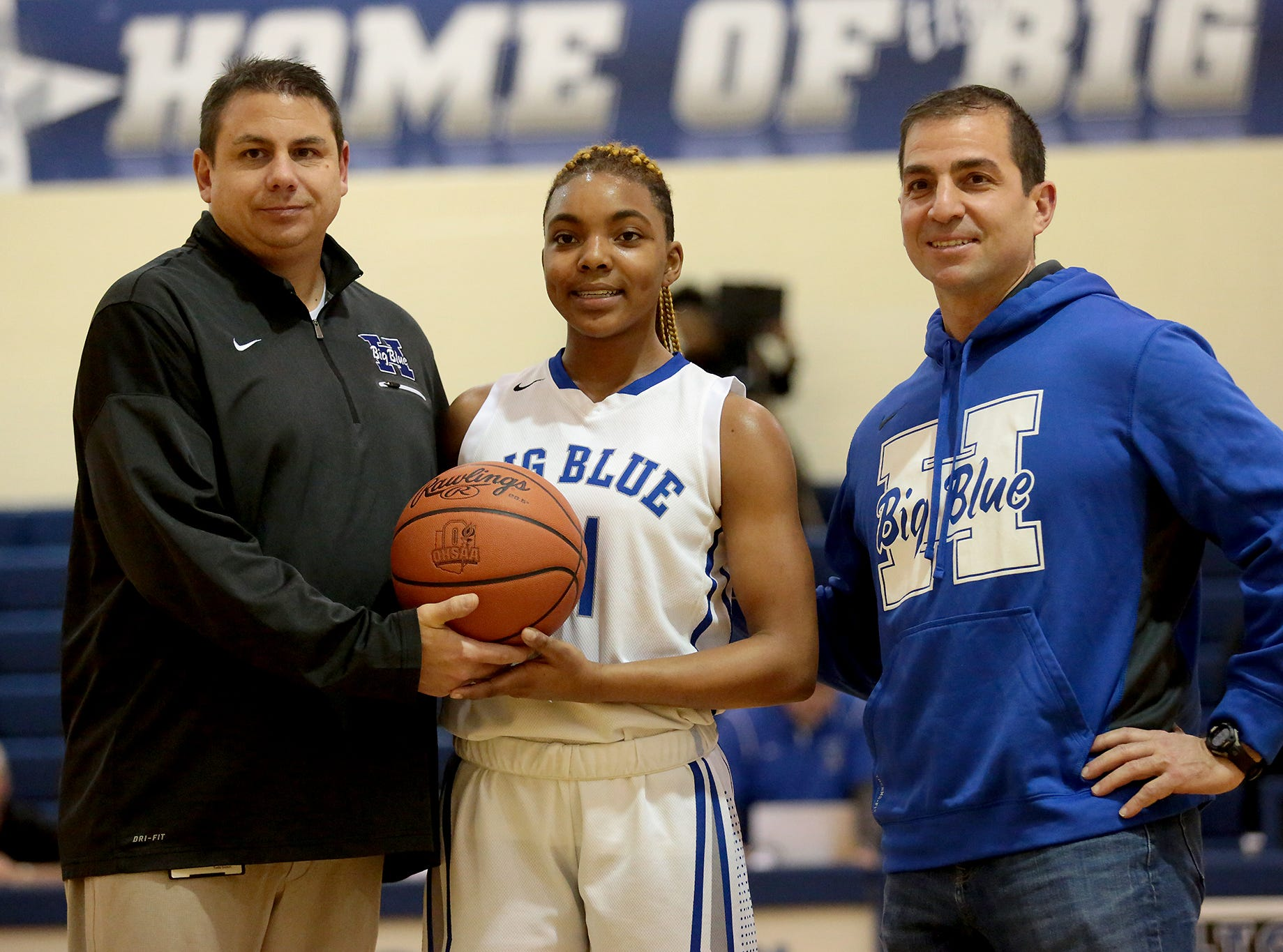 Hamilton City Schools district athletic director Todd Grimm and Hamilton High principal John Wilhelm honor Big Blue senior CiCi Riggins after she became Hamilton High's leading scorer for girls basketball during their game against Northwest at the Hamilton freshman school Thursday, Dec. 27, 2018.