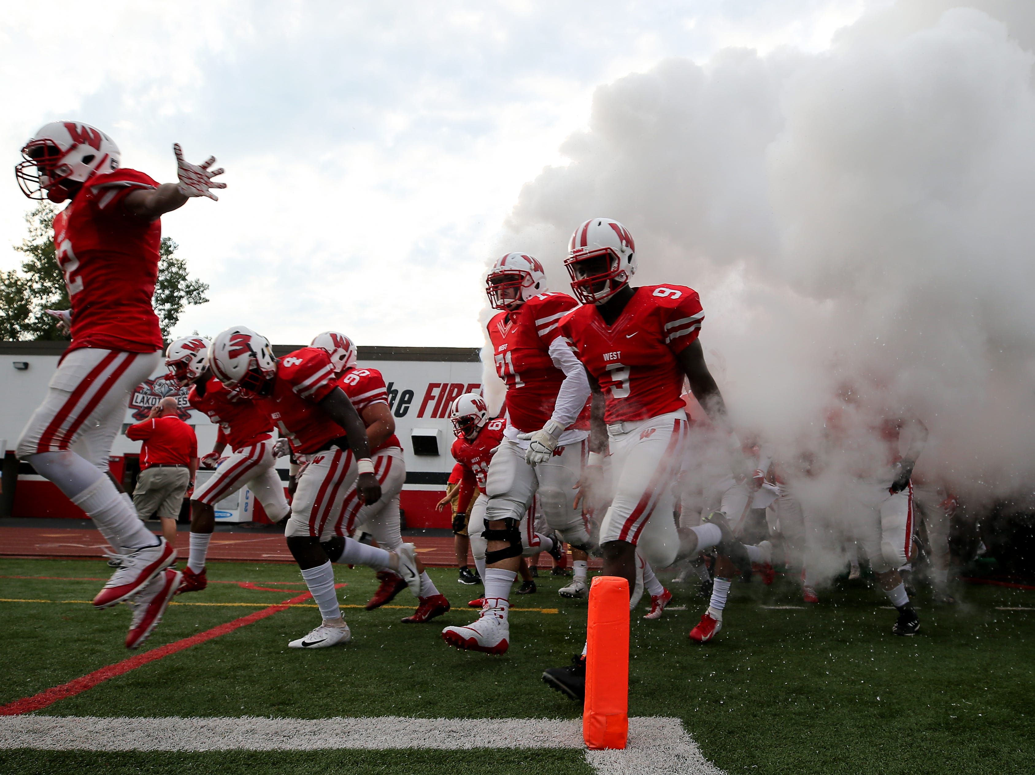 The Lakota West Firebirds take the field before kickoff of a high school football game between the Oak Hills Highlanders and Lakota West Firebirds, Friday, Sept. 21, 2018, at Lakota West High School in West Chester Township, Ohio.