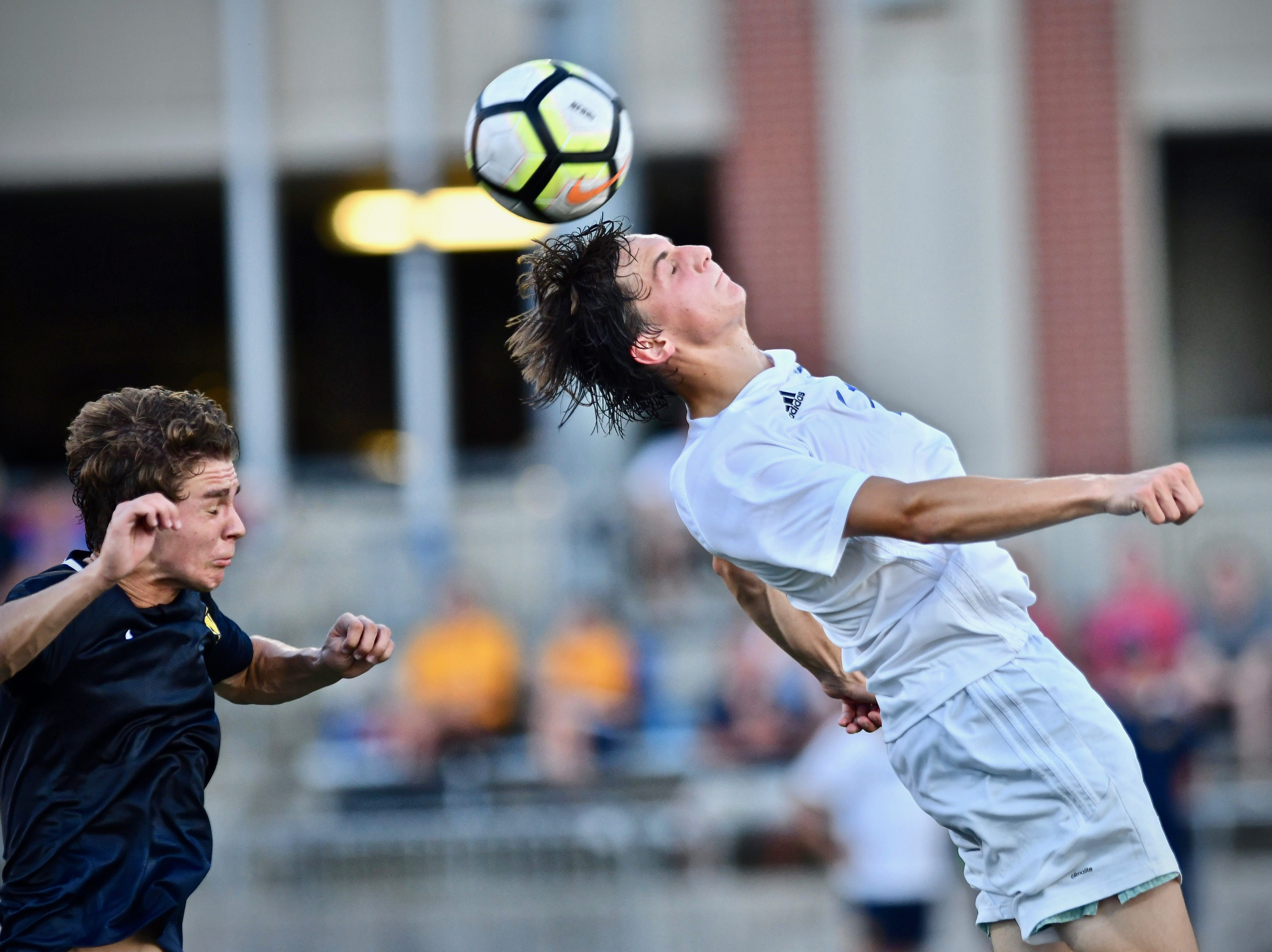 St. Xavier's Gino Geiser battles for a ball at midfield against Moeller Tuesday, Sept. 4, 2018 at Gettler Stadium on the campus of the University of Cincinnati