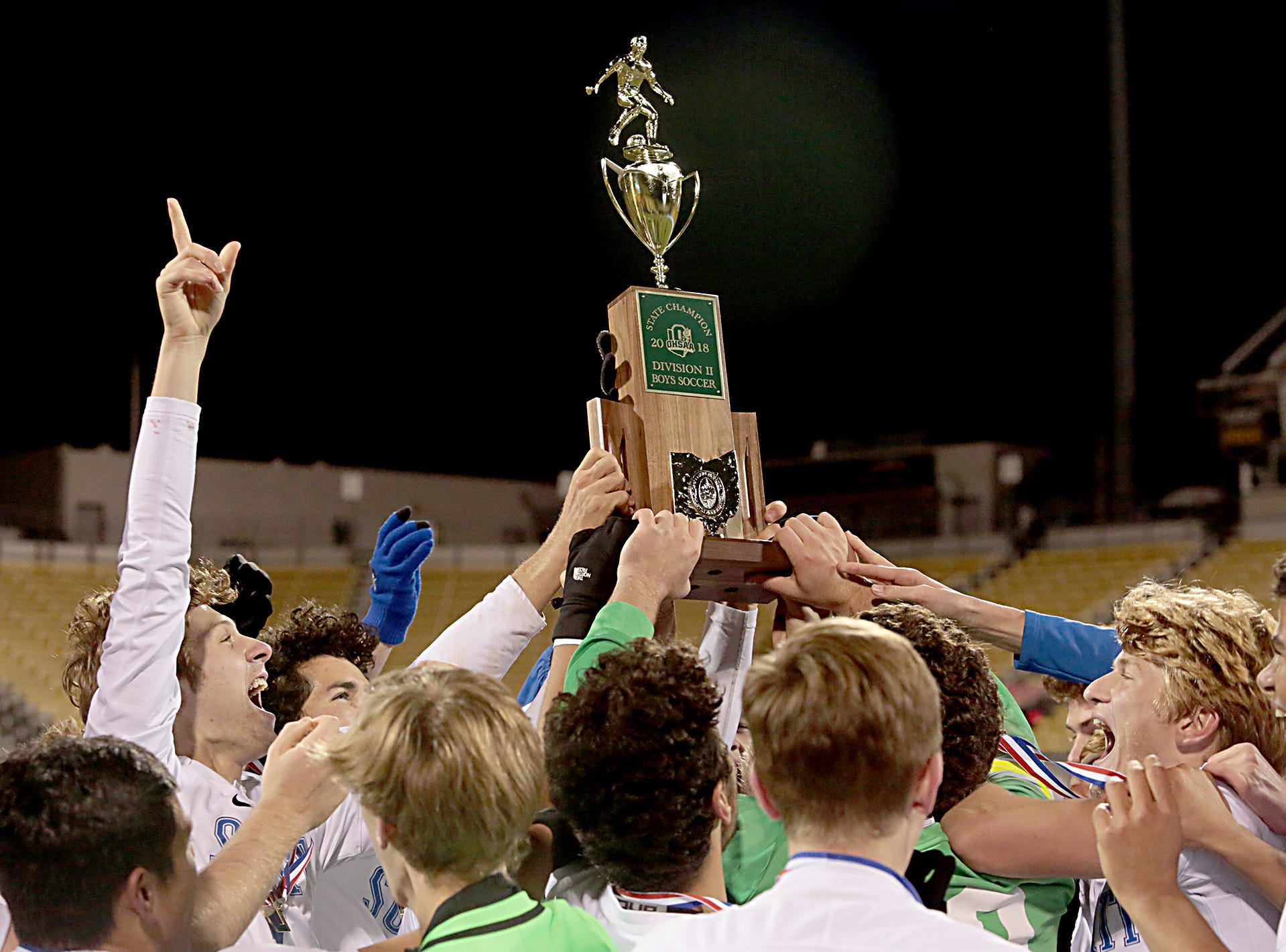 The Summit Country Day Silver Knights take possession of the boys Division II state championship trophy after defeating Revere at MAPFRE Stadium in Columbus Saturday, Nov. 10, 2018.