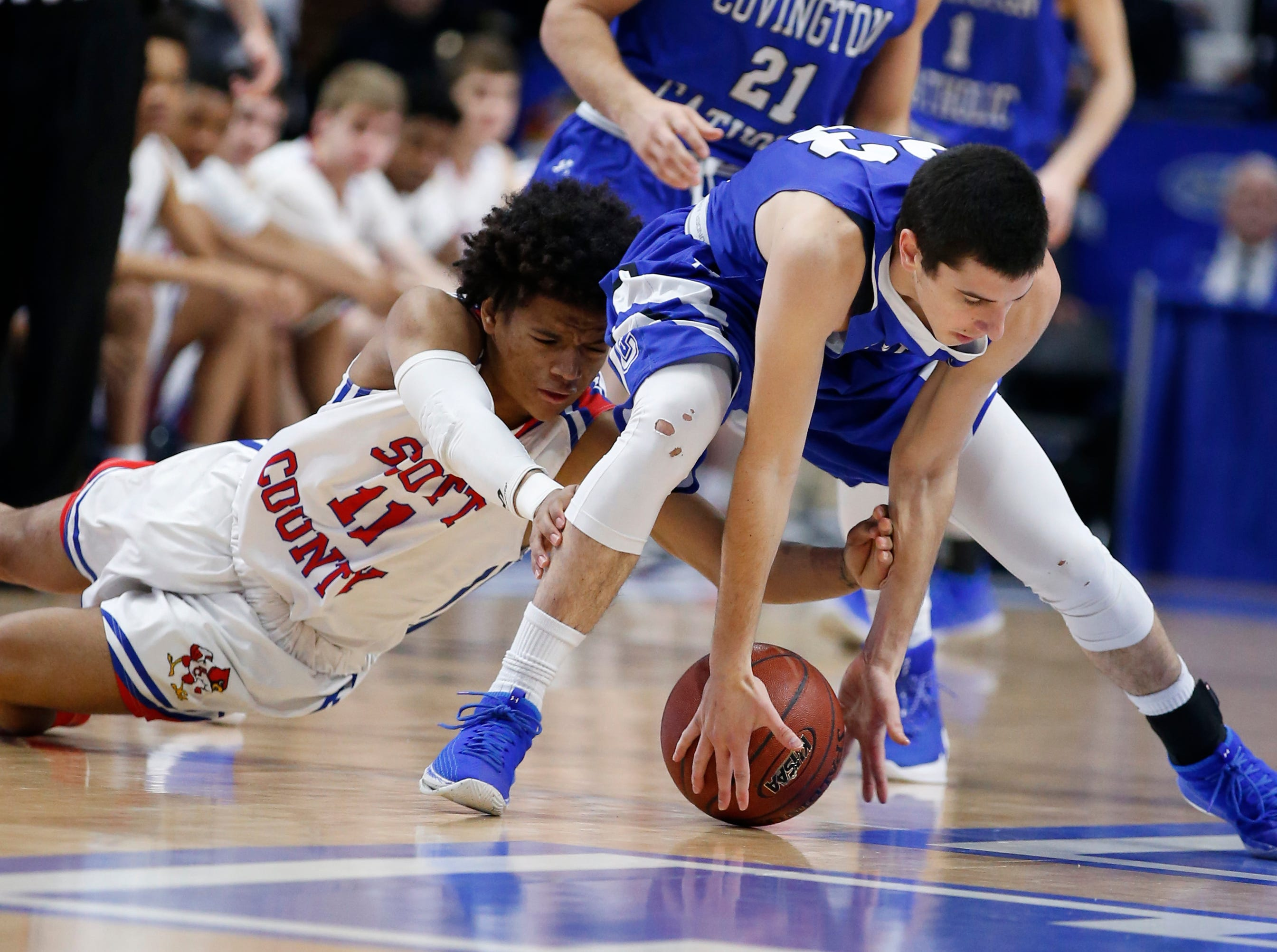 Covington Catholic's Casey Nowak, 23, right, scoops up a loose ball in front of Scott County's Diablo Stewart, 11, left, during the championship game of the Whitaker Bank/KHSAA Boys' Sweet 16 basketball tournament played at Rupp Arena in Lexington, Ky. Sunday March 18, 2018.