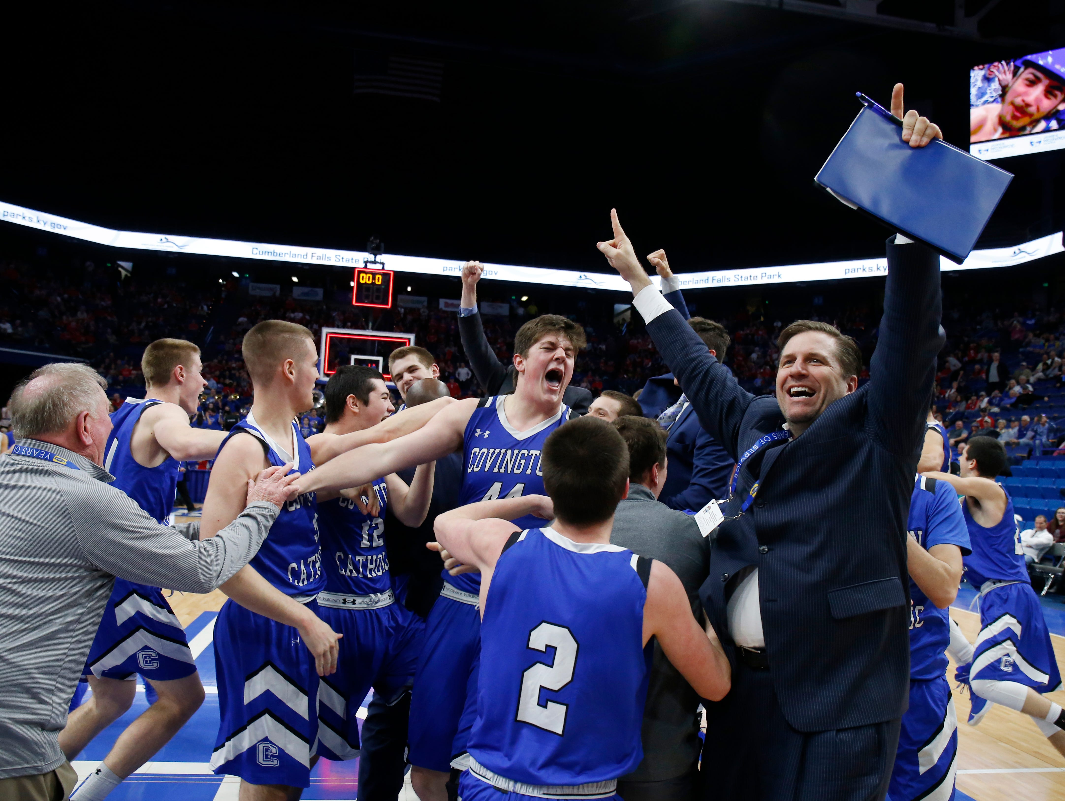 Covington Catholic celebrates their win over Scott County in the championship game of the Whitaker Bank/KHSAA Boys' Sweet 16 basketball tournament played at Rupp Arena in Lexington, Ky. Sunday March 18, 2018.
