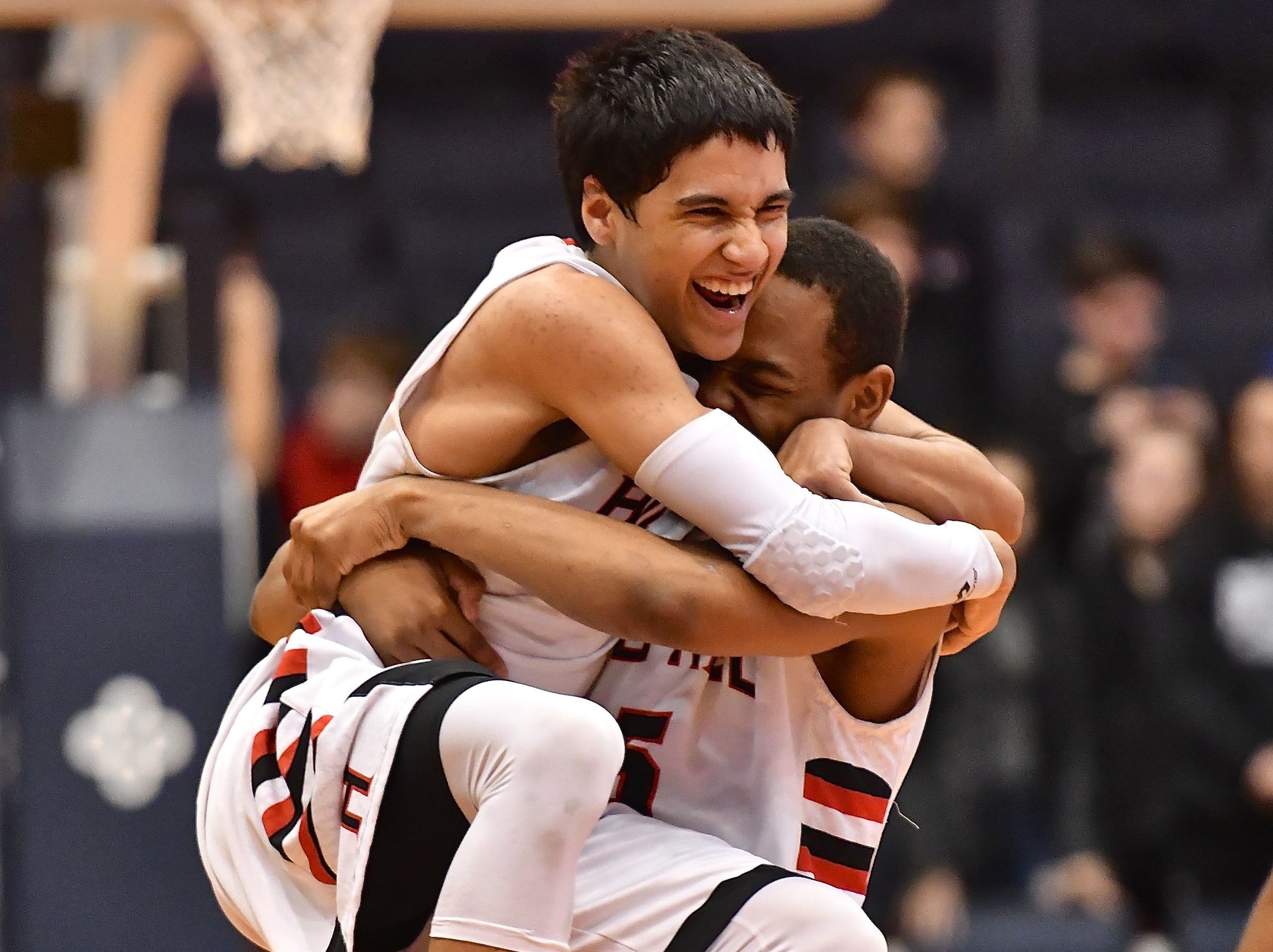 Hughes' Giovanni Santiago leaps into the arms of AJ Smith as the final buzzer sounds Thursday, March 8 at the University of Dayton.