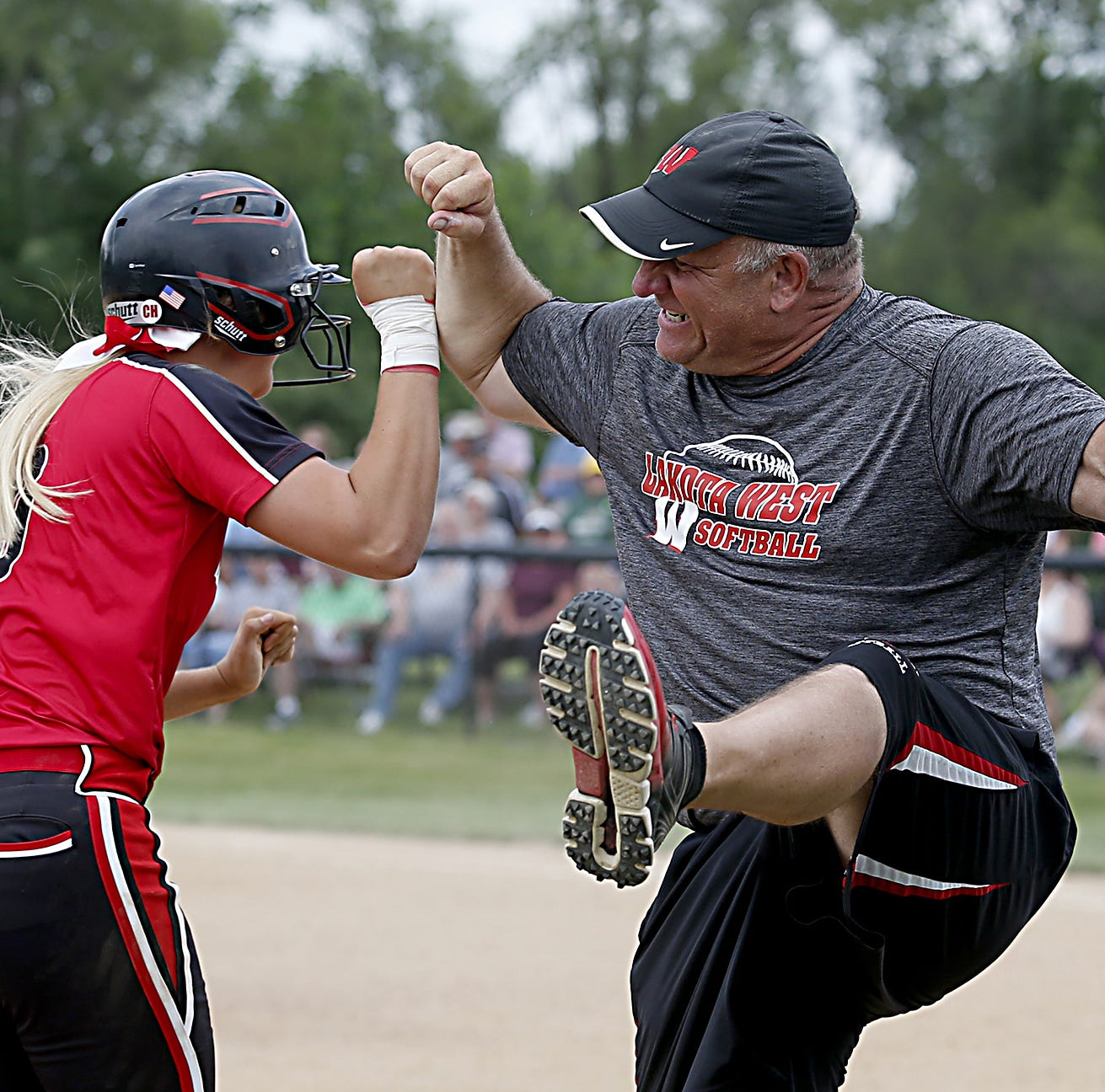 Lakota West batter Alyssa Triner is greeted by head coach Keith Castner after her two-run home run against Lebanon during their Division I regional softball final at Centerville Saturday, May 26, 2018.